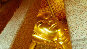 Reclining Buddha gold statue and thai art architecture Stock Image