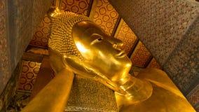 Reclining Buddha gold statue and thai art architecture Stock Photo