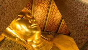 Reclining Buddha gold statue and thai art architecture Royalty Free Stock Images