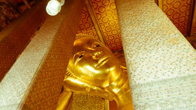 Reclining Buddha gold statue and thai art architecture Stock Photography