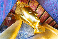 Reclining Buddha gold statue and thai art architecture. Stock Image