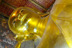 Reclining Buddha gold statue and thai art architecture. Royalty Free Stock Photo