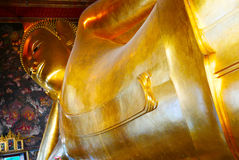 Reclining Buddha gold statue and thai art architecture. Royalty Free Stock Photos