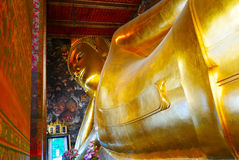 Reclining Buddha gold statue and thai art architecture. Stock Images