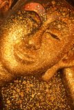 Reclining Buddha image covered with gold leaves Stock Photography