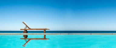 Free Reclining Chair Near A Swimming Pool, Sea Blue Sky Panoramic Background Royalty Free Stock Photos - 114131578