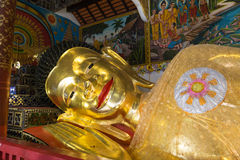 Reclining golden buddha statue. Smiling face of reclining golden buddha statue in asian temple Stock Photography