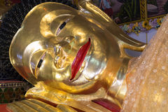 Reclining golden buddha statue. Smiling face of reclining golden buddha statue in asian temple Royalty Free Stock Photography