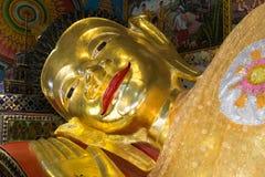 Reclining golden buddha statue. Smiling face of reclining golden buddha statue in asian temple Stock Photos