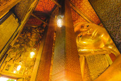 Reclining golden Buddha statue with thai art architecture in church Wat Pho. Temple of the Reclining Buddha in Bangkok,Thailand royalty free stock photography