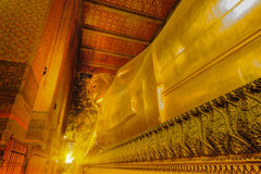 Reclining golden Buddha statue with thai art architecture in church Wat Pho Stock Image