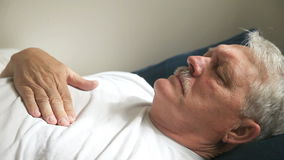 Reclining man with chest pain. Senior man lying down suffering from pains in his chest stock video