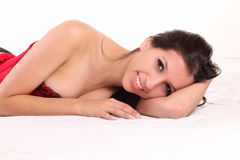Reclining young caucasian woman red corset smiling Royalty Free Stock Photo