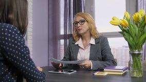 Reclutador sonriente en una entrevista de trabajo que mira el CV metrajes