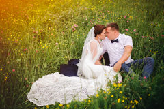 Recém-casados despreocupados que encontram-se no prado do por do sol Imagem de Stock