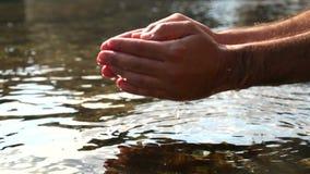 Recogida del agua con las manos en el mar