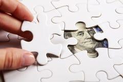 Recogida del billete de banco del dólar con el rompecabezas Imagen de archivo libre de regalías