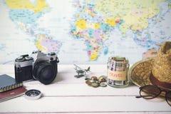 Recogida del dinero para el viaje con los accesorios del viajero foto de archivo