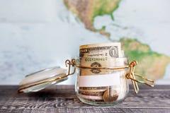 Recogida del dinero para el viaje Lata de cristal usada como moneybox Imagenes de archivo