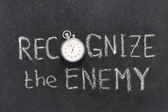 Recognize the enemy. Phrase handwritten on chalkboard with vintage precise stopwatch used instead of O Stock Photography