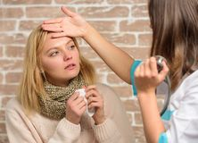 Recognize symptoms of cold. Remedies should help beat cold fast. Tips how to get rid of cold. Woman feels badly ill. Sneezing. Girl in scarf hold tissue while royalty free stock image
