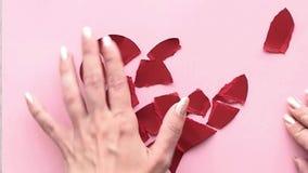 Recoja el corazón quebrado La mano femenina recoge el corazón rasgado a los pedazos almacen de video