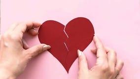 Recoja el corazón quebrado La mano femenina recoge el corazón rasgado a los pedazos almacen de metraje de vídeo