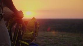 Recoja las cosas en el viaje El hombre pone cosas en un alza, las pone en una mochila En la puesta del sol almacen de metraje de vídeo