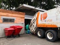 Recolector del trabajador y un camión de basura parqueado en contenedor industrial foto de archivo