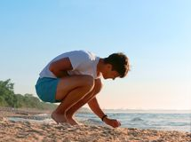 Recolha pedras na costa de mar, o menino recolhe pedras no mar, homem novo que descansa na costa de mar fotos de stock