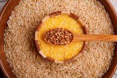 Recolhendo cereais secos Trigo mourisco, arroz, trigo em uma grande placa marrom fotografia de stock