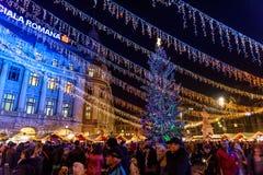 Recolhimento dos povos na cidade do centro de Bucareste do mercado do Natal na noite Imagem de Stock Royalty Free