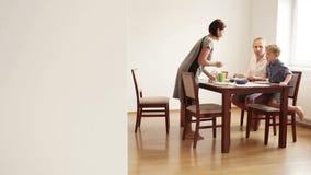 Recolhimentos da família na tabela para o café da manhã: a mãe está servindo o alimento vídeos de arquivo