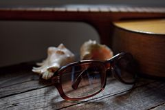 Recollection of summer, guitar, sunglasses and shells from the sea Stock Photography
