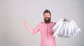 Recommendation concept. Hipster on smiling face recommends to buy. Man with beard and mustache carries bunch of shopping. Bags, grey background. Guy shopping on stock images