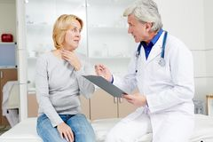 Recommendations of doctor. Female patient complaining to doctor about sore throat and other symptoms of flu Royalty Free Stock Image
