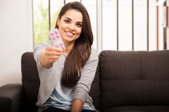 Recommending some medicine. Beautiful young Hispanic woman recommending and handing over some pills to the camera. Focus on woman Stock Photography
