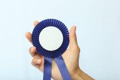 A recompensa azul assina dentro uma mão Fotos de Stock Royalty Free
