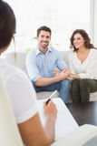 Reconciled couple smiling on couch. In the therapist office Royalty Free Stock Photos