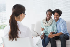 Reconciled couple smiling at their therapist Stock Image