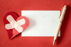 Reconciliation concept. Broken heart fixed with a plaster and empty card for text royalty free stock image