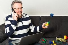 Reconciliation of work and family life. Portrait of a middle aged man sitting in front of computer with toys and baby clothes on sofa, doing a phonecall and royalty free stock photo