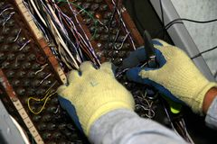 Reconnecting wires. Mechanic connecting telephone wires into old telephone terminal royalty free stock photo