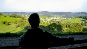 Reconstrucción en la naturaleza, odenwald, hombre joven que se sienta en un banco imagen de archivo
