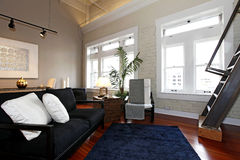 Reconstructed modern living room. Reconstructed modern living room with brick painted wall, hardwood floor and high ceiling. View of black classic couch Royalty Free Stock Photo