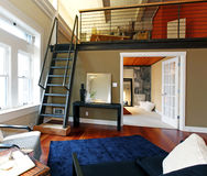 Reconstructed modern living room with mezzanine. View of modern reconstructed living room with mezzanine area above bedroom. View of iron steep stairs Royalty Free Stock Photography