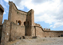 The reconstructed stony wall and the fragment of the tower in the medieval Genoese fortress. Royalty Free Stock Photo