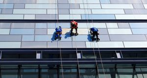 Reconstruction. Three men repairing the wall of the skyscraper Royalty Free Stock Photo
