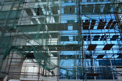Reconstruction building. Reconstruction modern building with green scaffold stock images