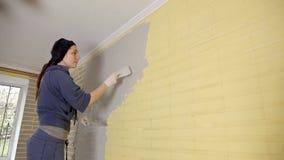 Reconstruction de la maison, construction des murs d'un mastic de jeune femme de la maison dans l'appartement avant la peinture clips vidéos